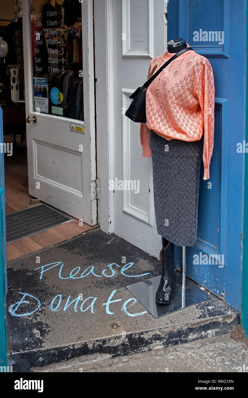 Mannequin at the door of a chariry shop in Stockbridge, Edinburgh, with the words 'Please Donate' chalked on the ground. - Stock Image
