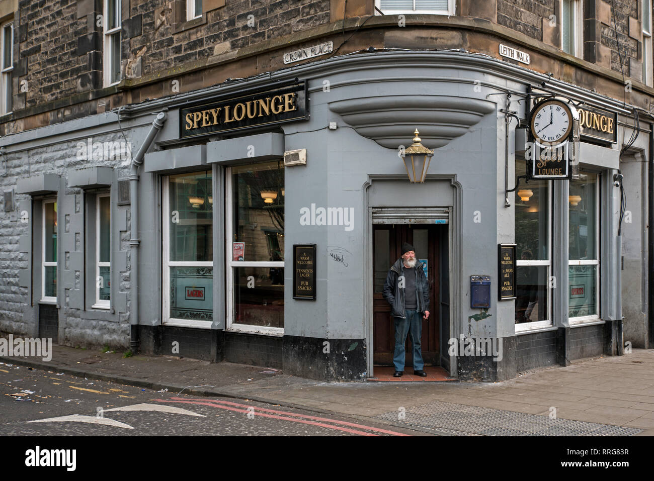 A customer stands in the doorway of the Spey Lounge public house on Leith Walk in Edinburgh, Scotland, UK. - Stock Image