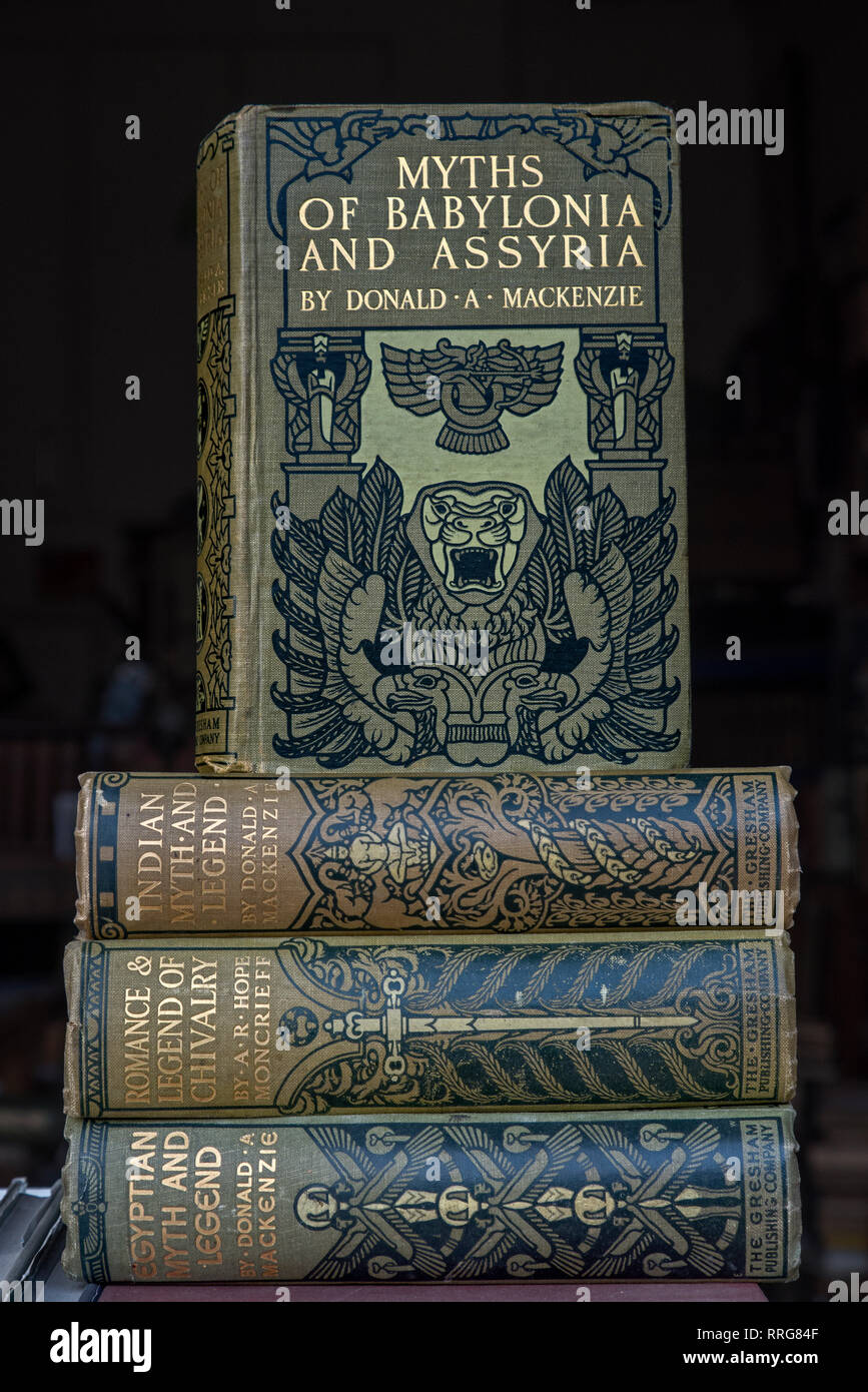 A pile of vintage books on various myths and legends, written by Donald A MacKenzie, in the window of a secondhand bookshop in Edinburgh. - Stock Image
