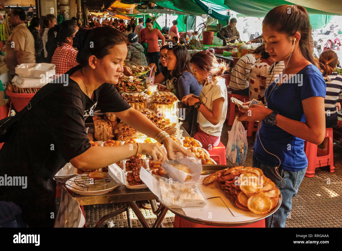 Girl wearing headphones buys food in the eating area of this huge old market, Central Market, city centre, Phnom Penh, Cambodia, Indochina - Stock Image