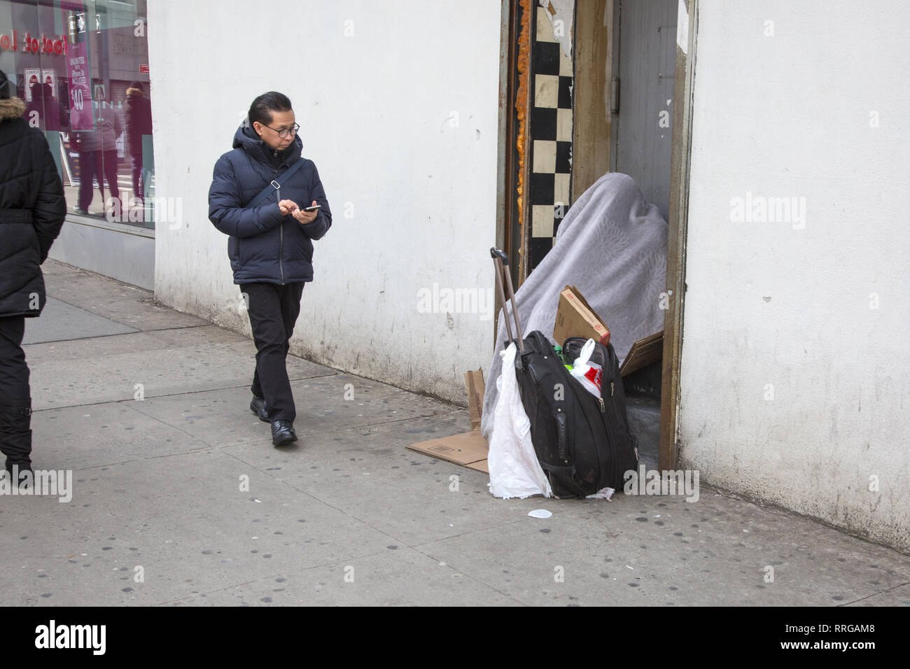 Anonymous homeless person in a doorway, downtown Brooklyn, New York. - Stock Image