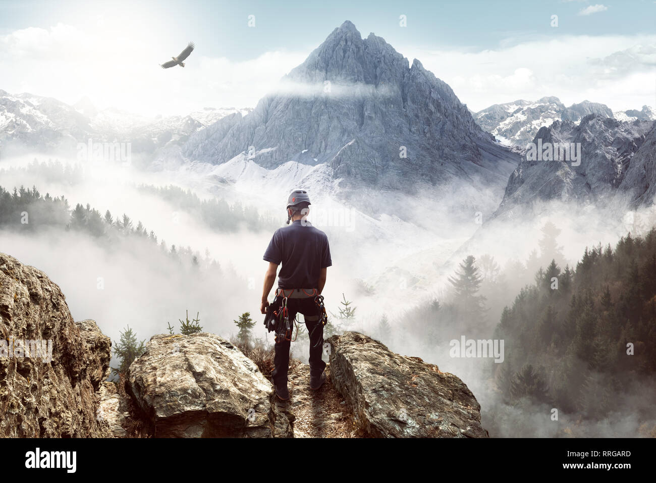 Young climber enjoying the view from the top of a mountain Stock Photo