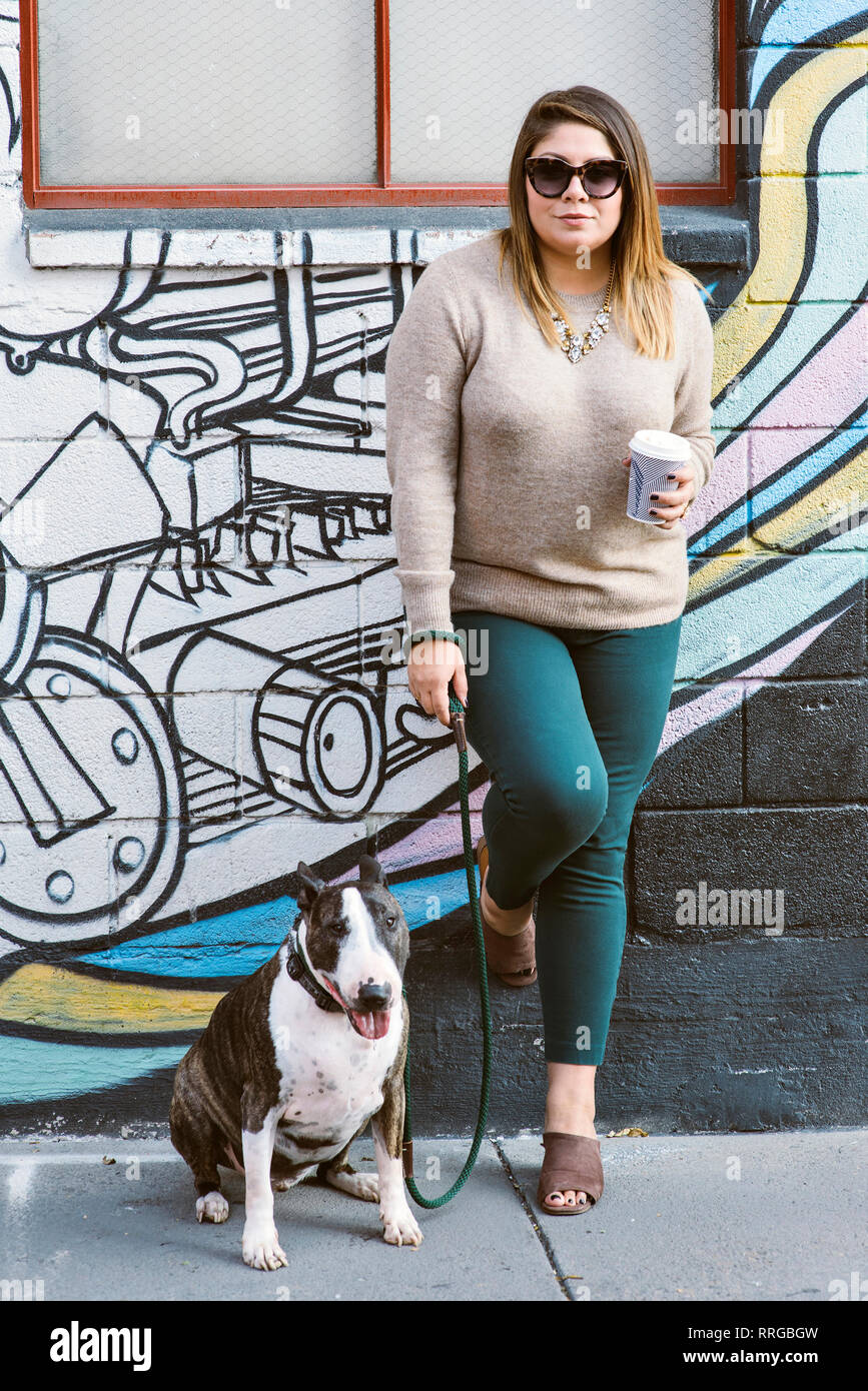 View of a woman with a coffee cup while standing next to her pet dog - Stock Image