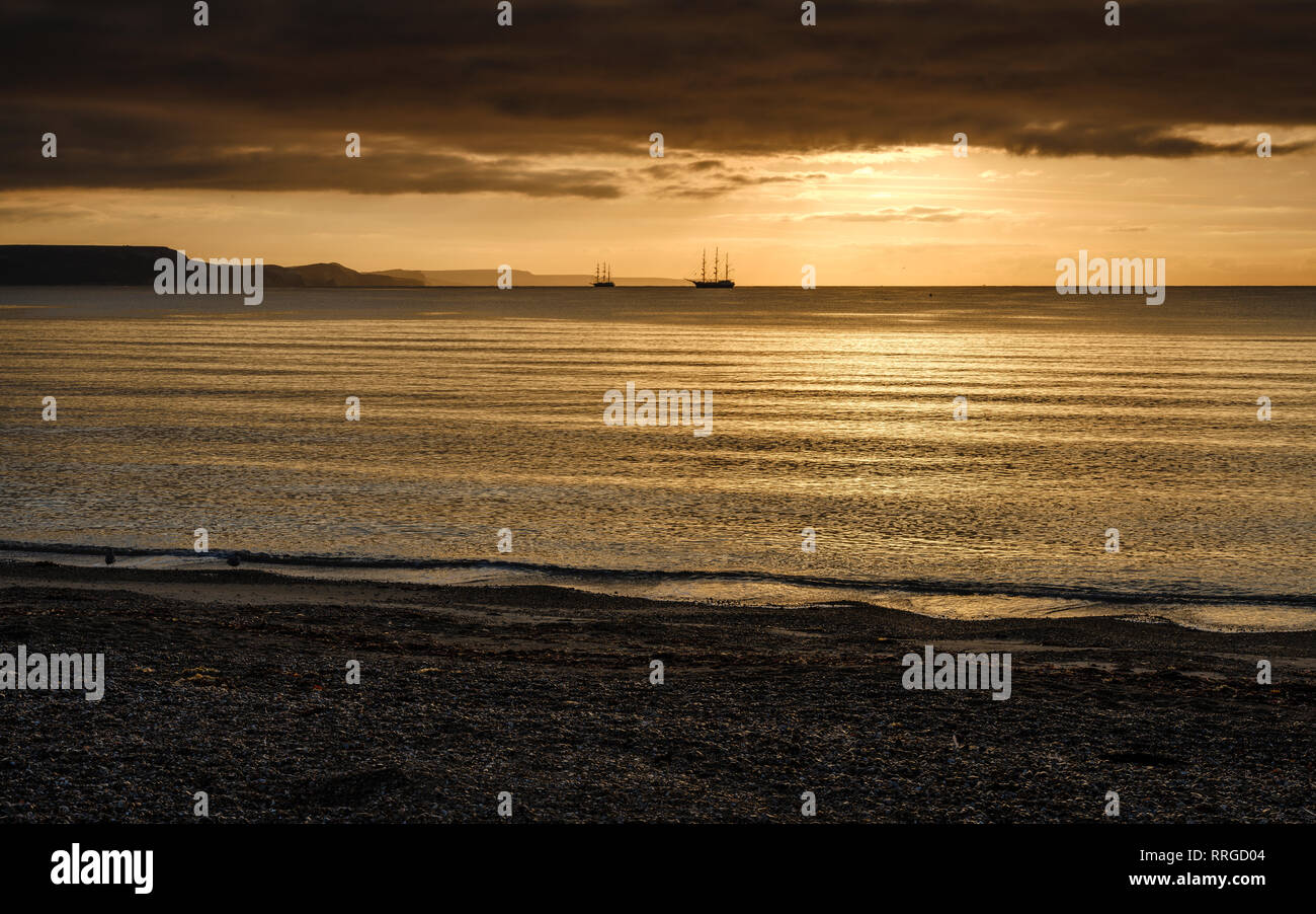Two square rigger sailing vessels at anchor on a shimmering sea, adjacent to the Jurassic Cliffs, Weymouth, Dorset, England, United Kingdom, Europe - Stock Image