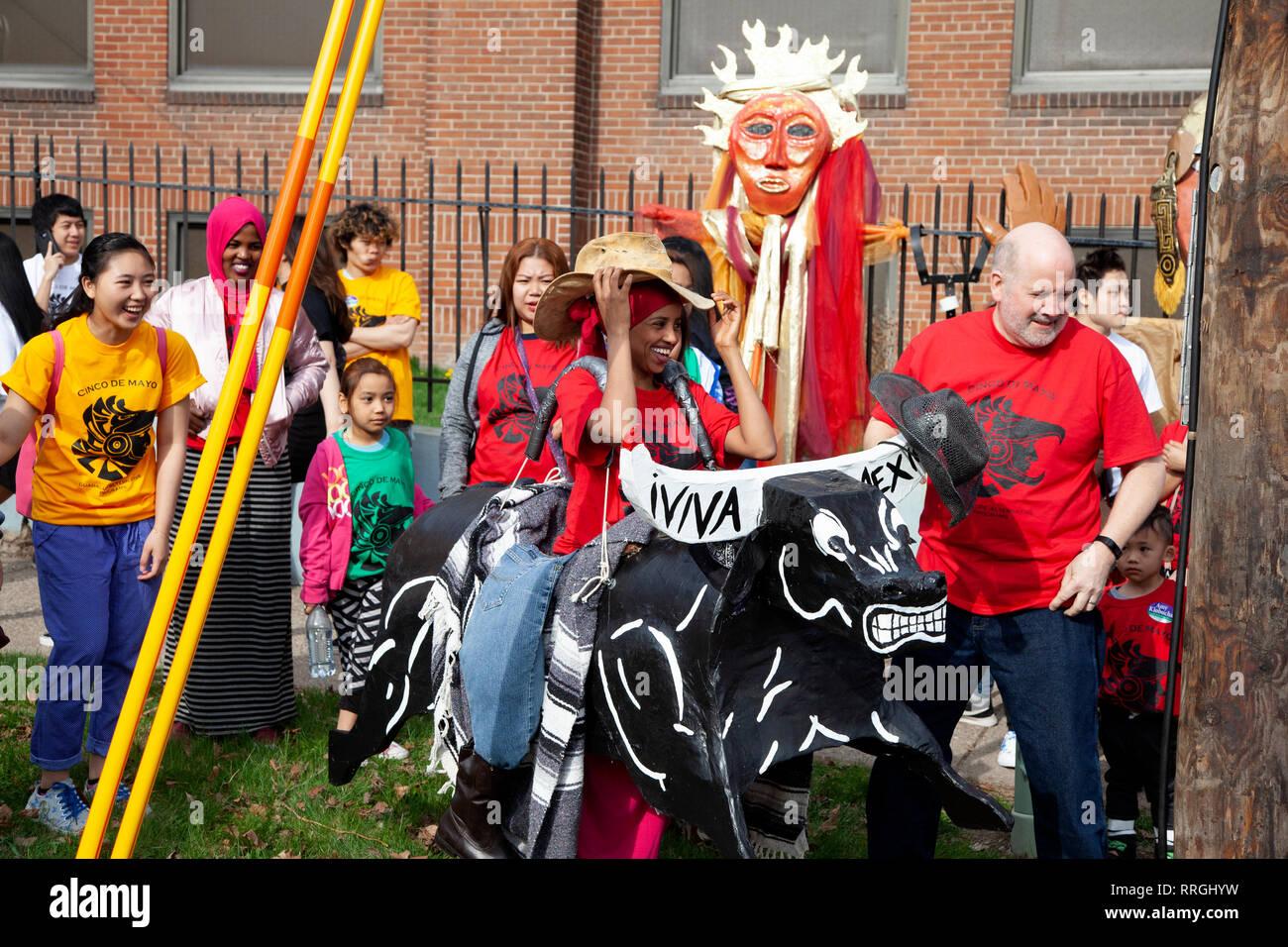 Guadalupe Alternative Programs School at Cinco de Mayo Parade Muslim woman wearing gaucho hat riding fierce cardboard bull. St Paul Minnesota MN USA - Stock Image