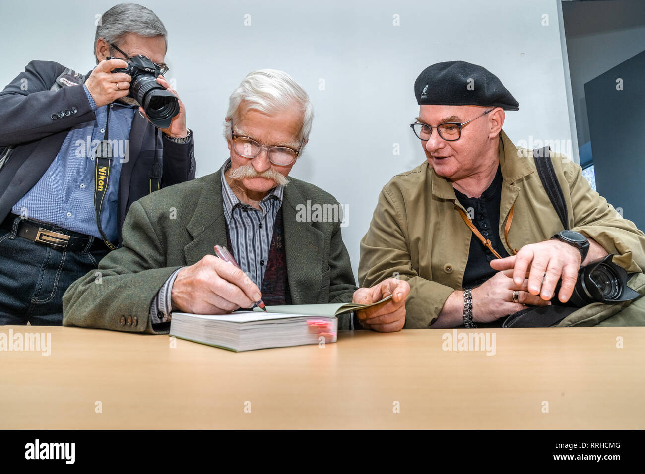 The international Vilnius Book Fair. H.Gudavičius (middle) author of the book about nature signs an autograph for the photographer A.Aleksandravičius - Stock Image