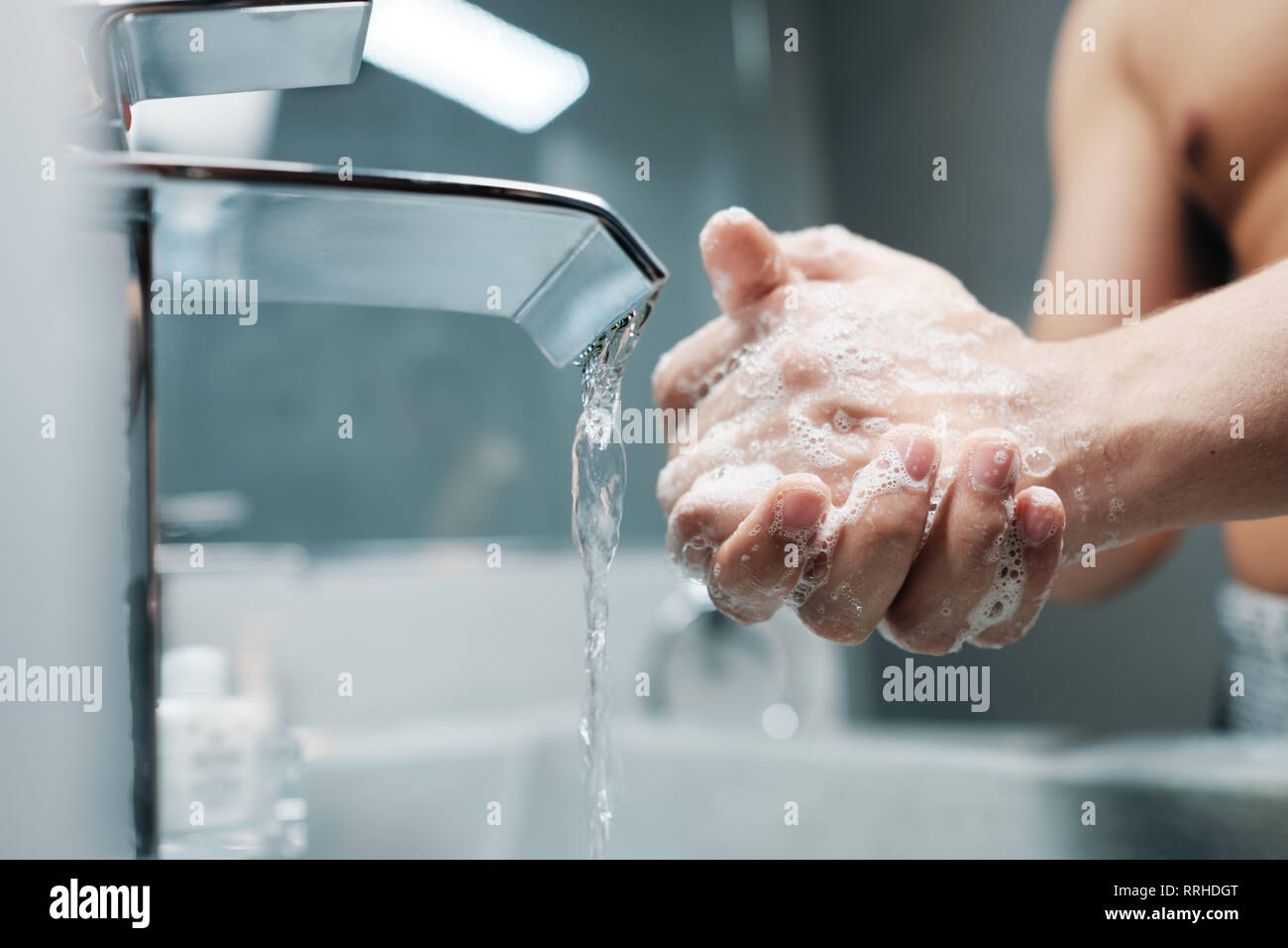 Man Washing Hands With Water And Soap In Bathroom - Stock Image