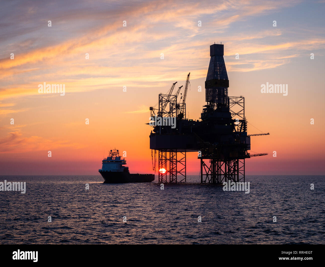A oil platform in the North sea with a supply vessel alongside during sunset. Stock Photo
