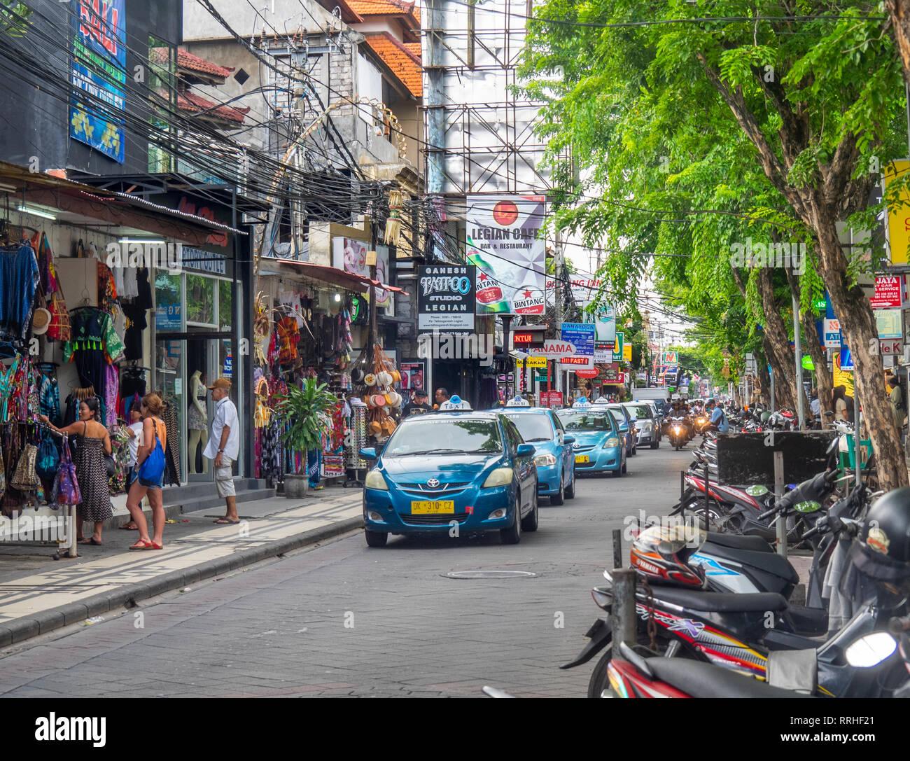 Bluebird taxis and local traffic in busy Jl Raya Legian in Kuta Bali Indonesia. - Stock Image