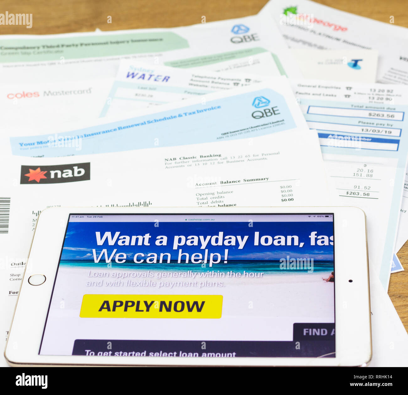 iPad and bills of Australian consumer looking at pay day lender site to pay household bills. Debt-stressed consumers are turning to payday finance. - Stock Image