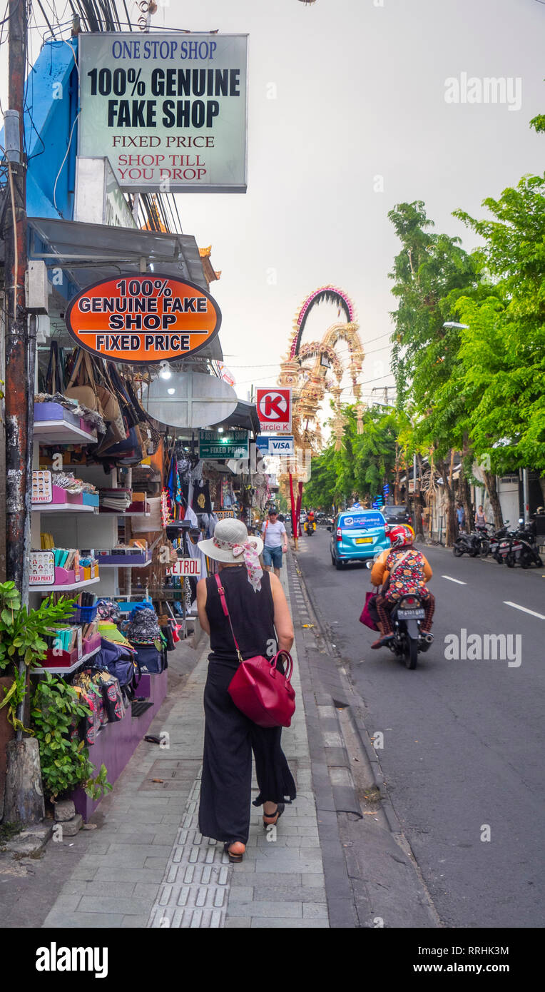 Caucasian female tourist with red bag walking past a humourous sign of 100% Genuine Fake Shop on Jl Raya Legian, Kuta Bali Indonesia. - Stock Image
