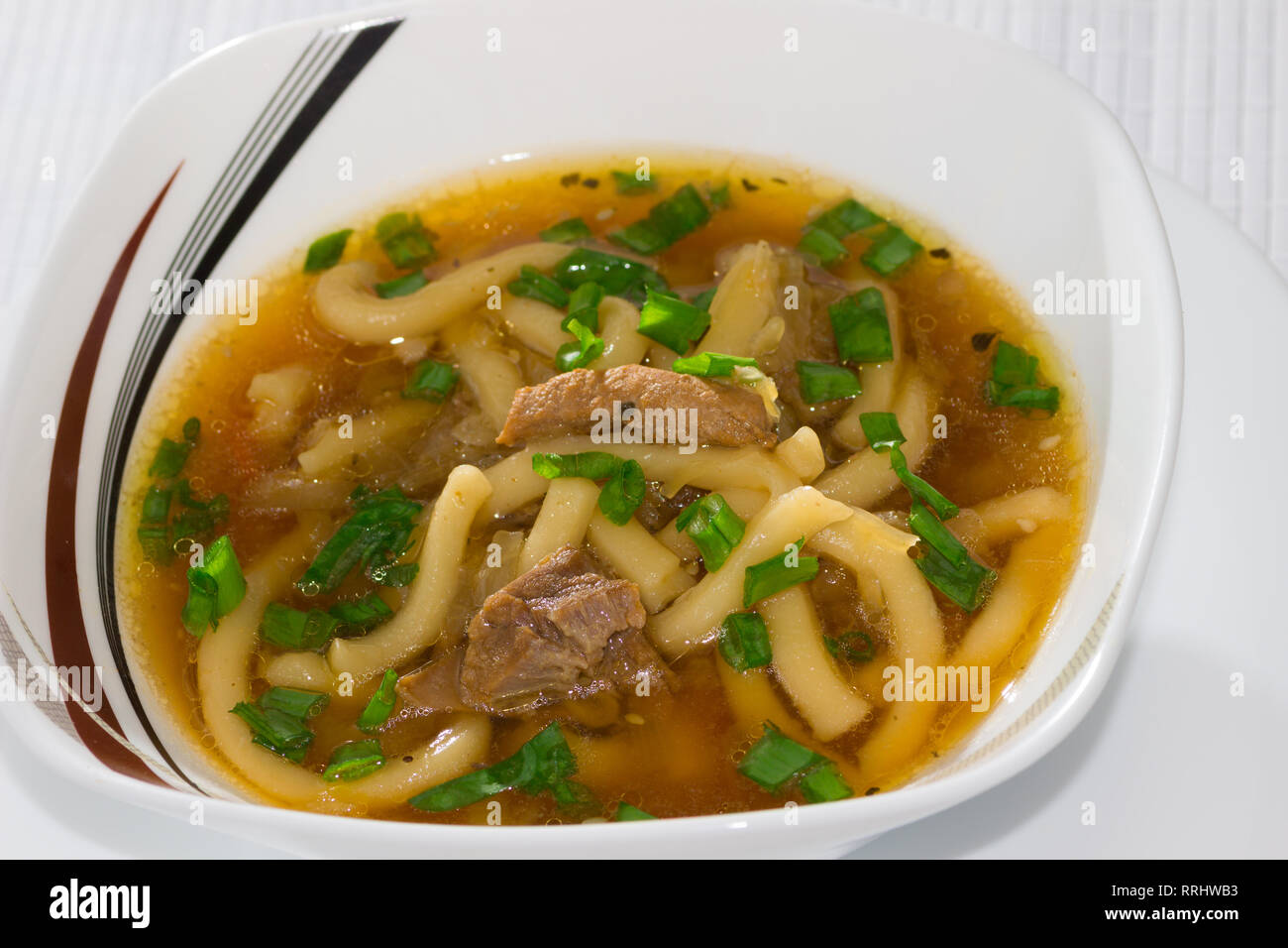 Bowl of miso soup with udon noodles, cabbage, pork and green onions with chopsticks on a bamboo napkin Stock Photo
