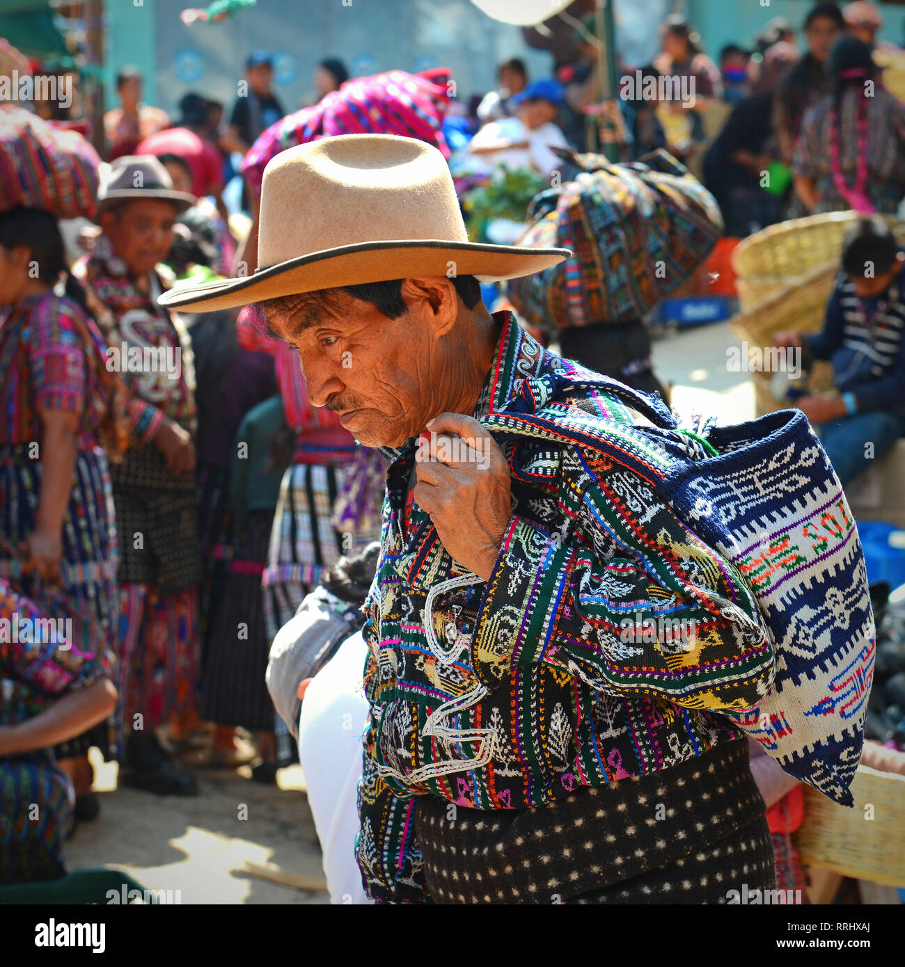 A portrait of a man in traditional clothing on the market of Solola with maya people in the background buying and selling goods, Guatemala. - Stock Image