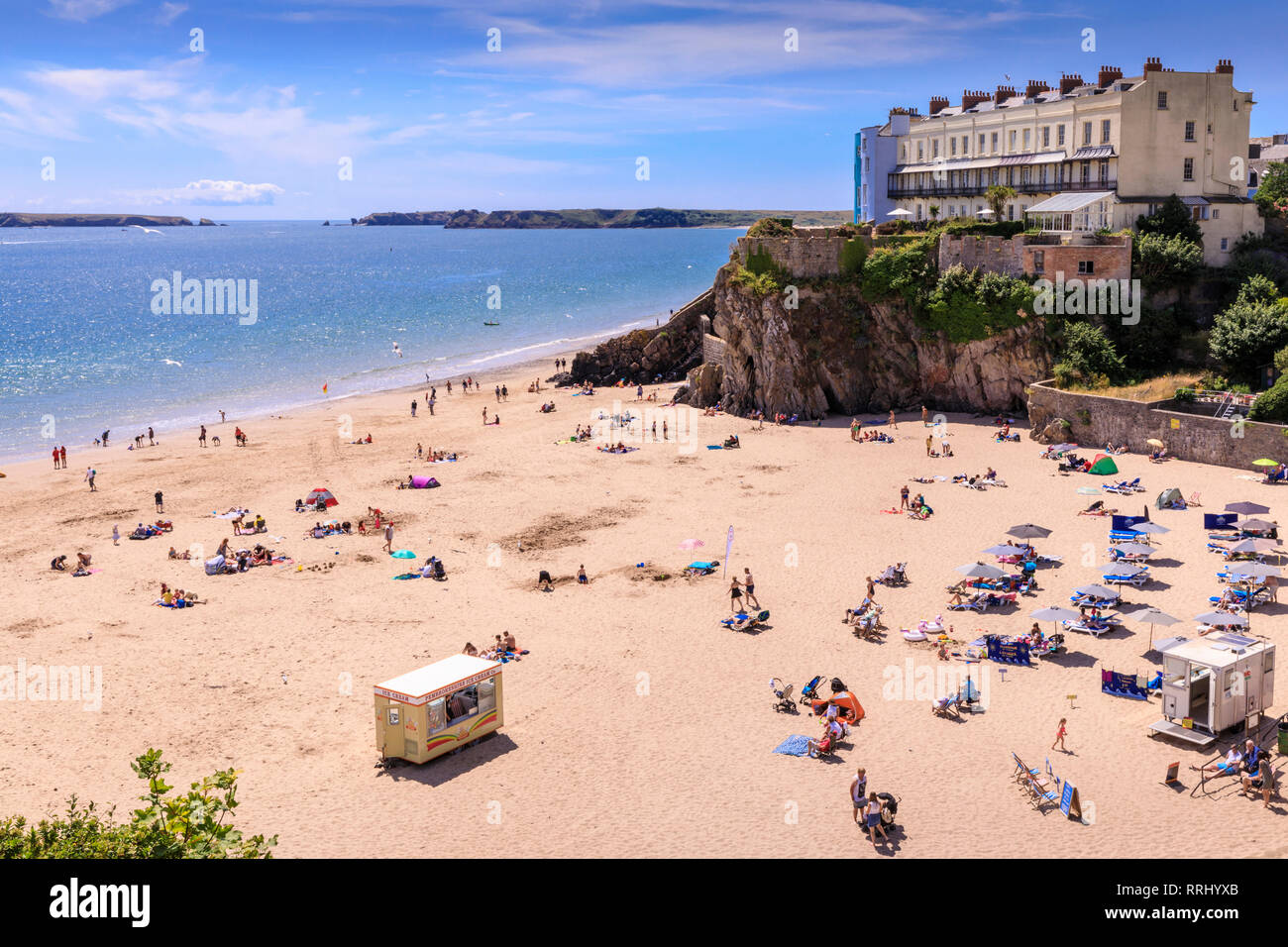 Castle Beach, historic houses above the cliffs, sunbathers on a sunny day in summer, Tenby, Pembrokeshire, Wales, United Kingdom, Europe - Stock Image