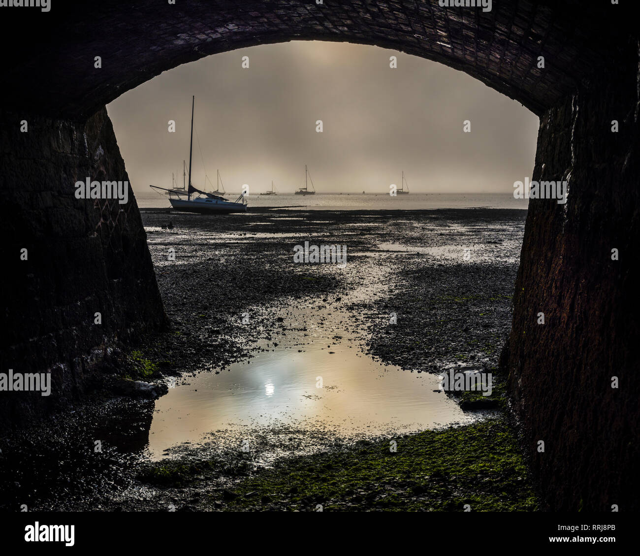 Boats on the Exe estuary in heavy fog viewed through an arch under the Exmouth to Penzance railway line, Starcross, Devon, England, United Kingdom - Stock Image