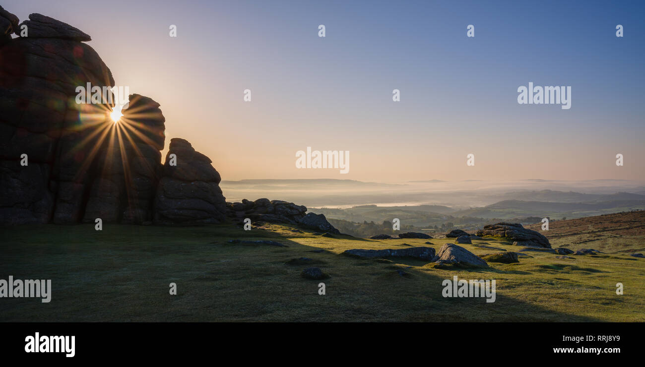 Sun breaks through a gap in granite rocks at Haytor in Dartmoor National Park, Bovey Tracey, Devon, England, United Kingdom, Europe - Stock Image