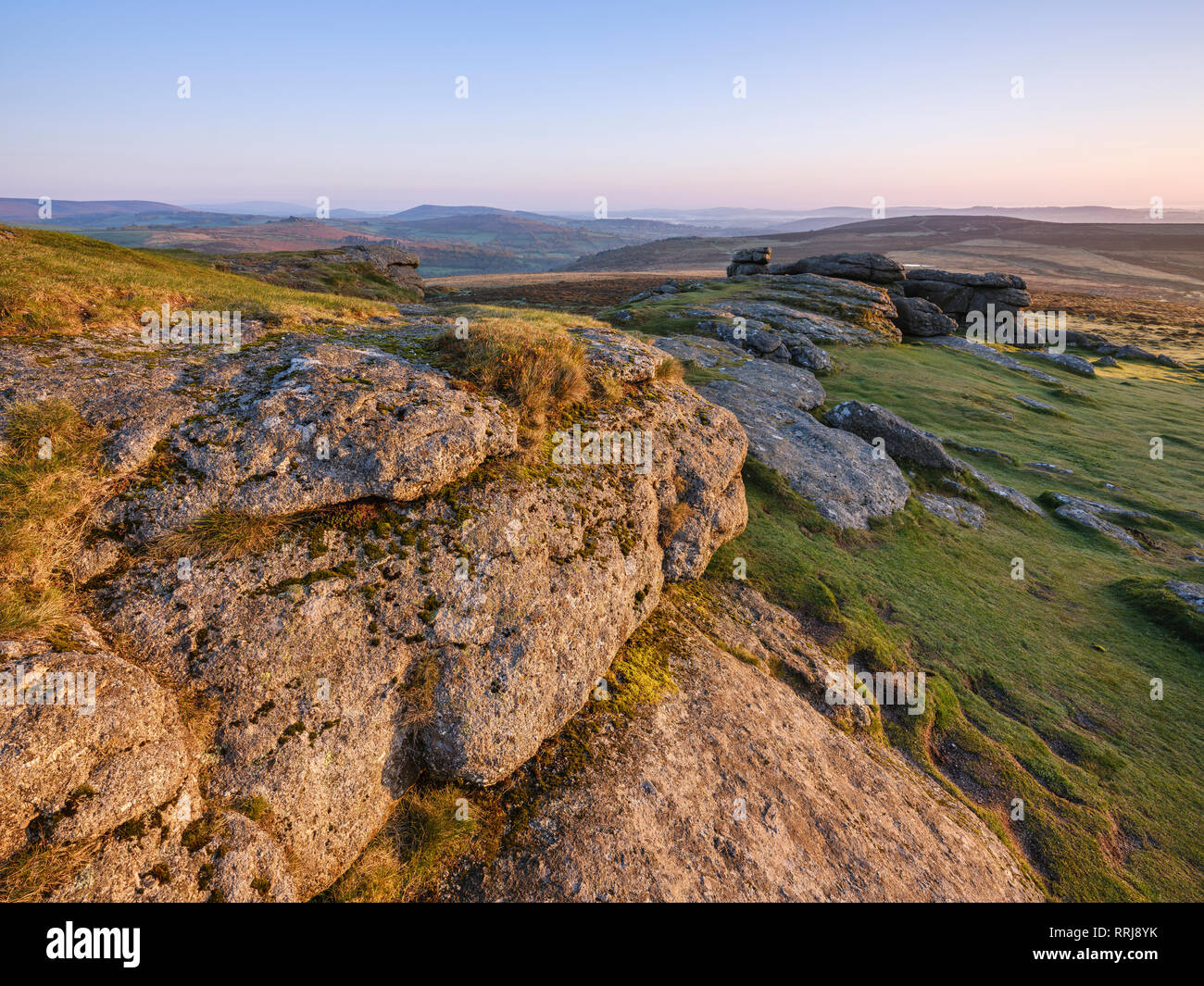 Warm sunlight on the granite summit of Saddle Tor in Dartmoor National Park, Bovey Tracey, Devon, England, United Kingdom, Europe - Stock Image