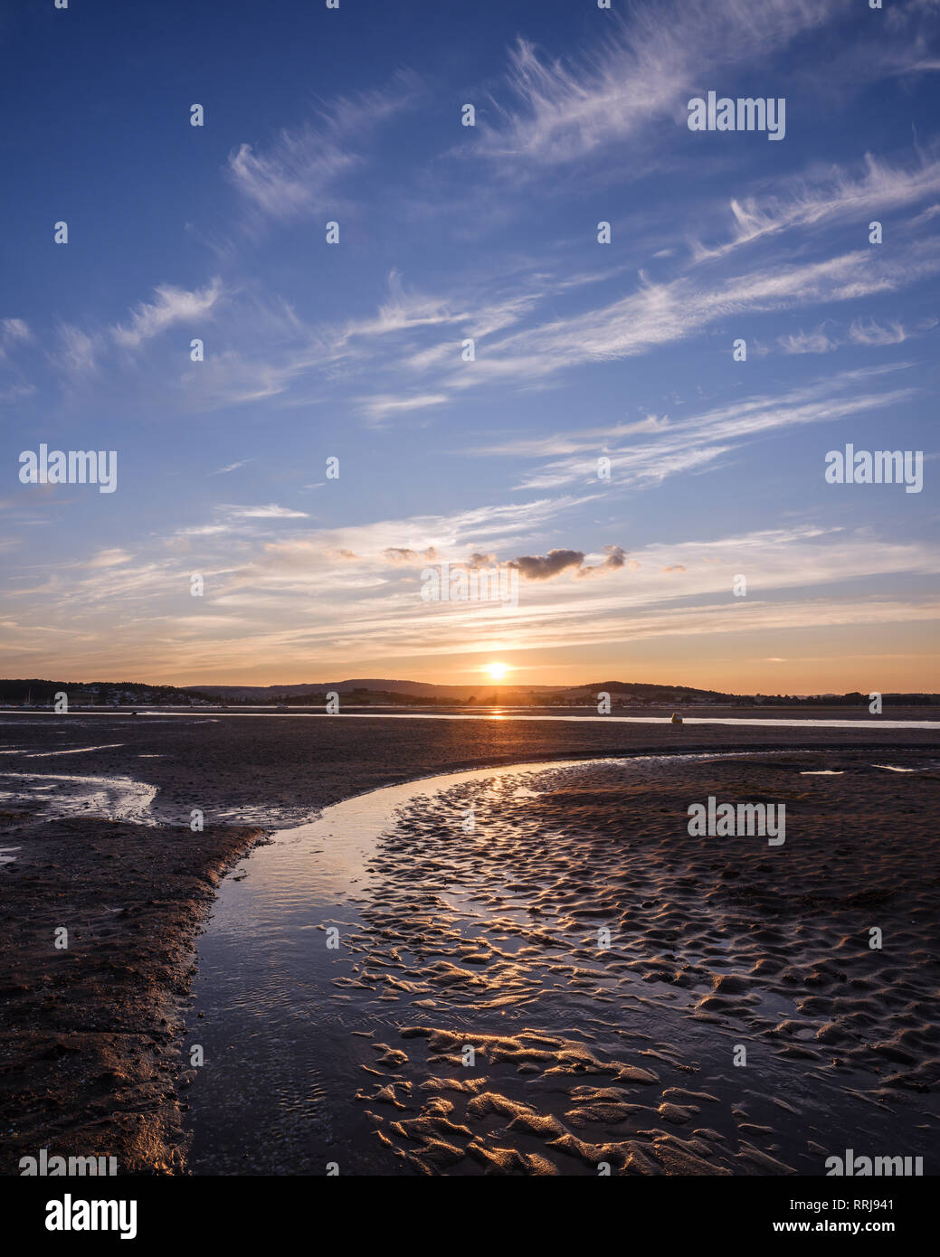 Looking at the setting sun across the Exe estuary towards Starcross from Exmouth, Devon, England, United Kingdom, Europe - Stock Image