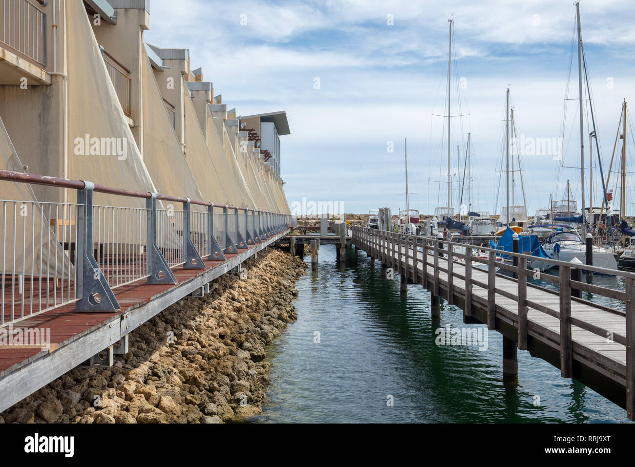 Walkways from the holiday apartments to the small boat harbour nearby with easy access, in the outskirts of Fremantle, Perth, Western Australia. - Stock Image