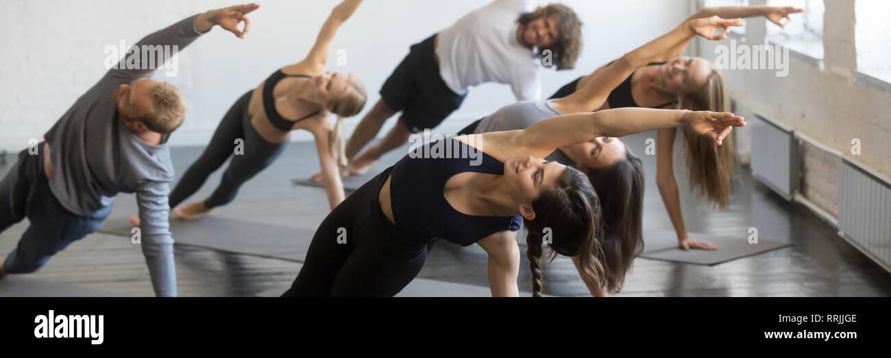 Girls and guys doing Side Plank pose yoga Vasisthasana exercise  Stock Photo