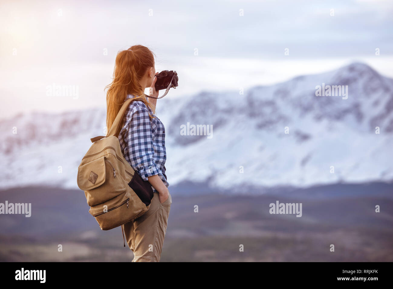 Beautiful woman with backpack is taking photo of mountain Stock Photo