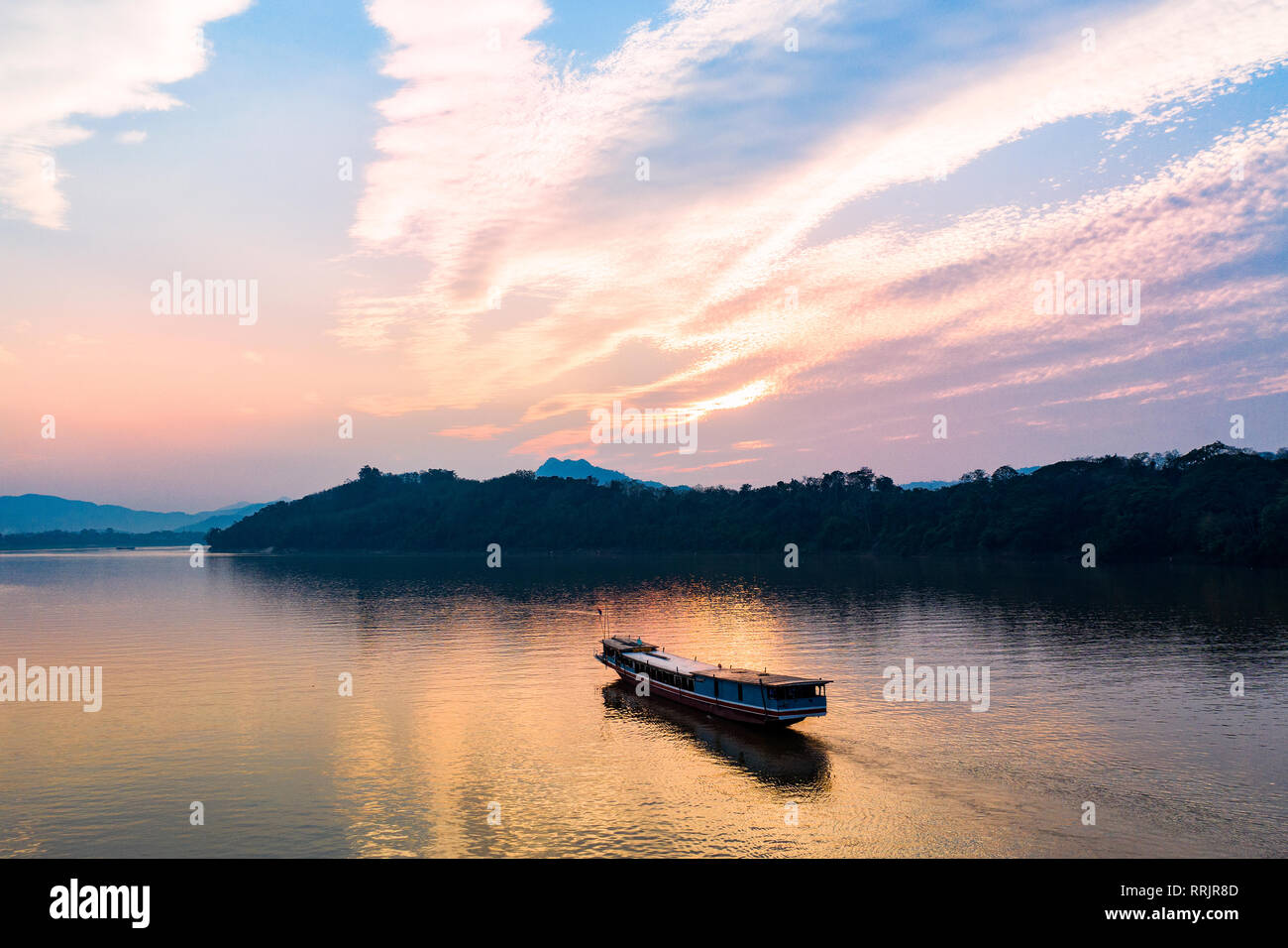(View from above) Stunning aerial view of a tourists boat sailing on the Mekong river at sunset, Luang Prabang, Laos. Stock Photo