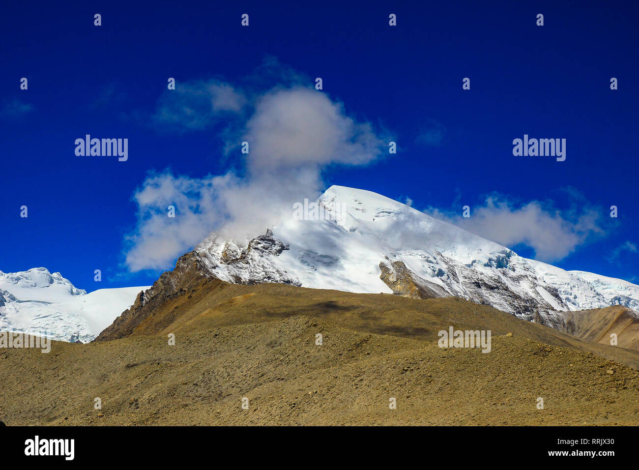 Landscape of deep blue sky and ice capped peaks of himalayan mountains with white clouds during day time - Stock Image
