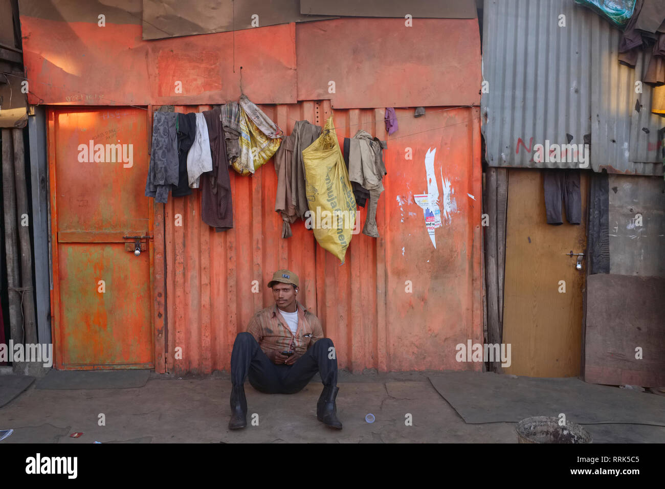 An exhausted worker in a dockyard in Mazgaon area, in Mumbai, India, relaxes in front of his living quarters, a rudimentary, if colorful,  tin shack - Stock Image