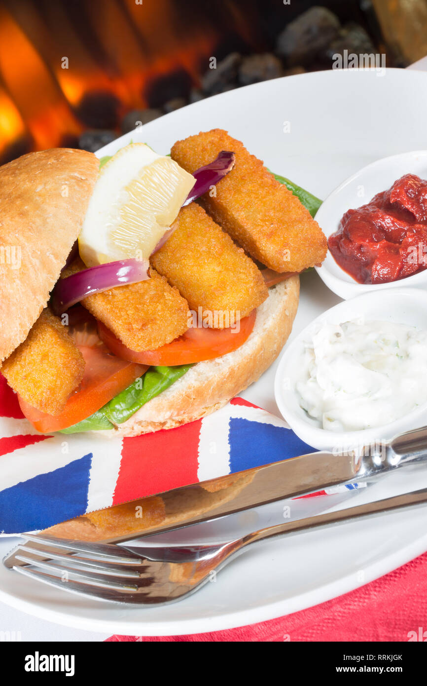 Typical English lunch snack of Fish fingers in a bun with ketchup and Tartar. - Stock Image