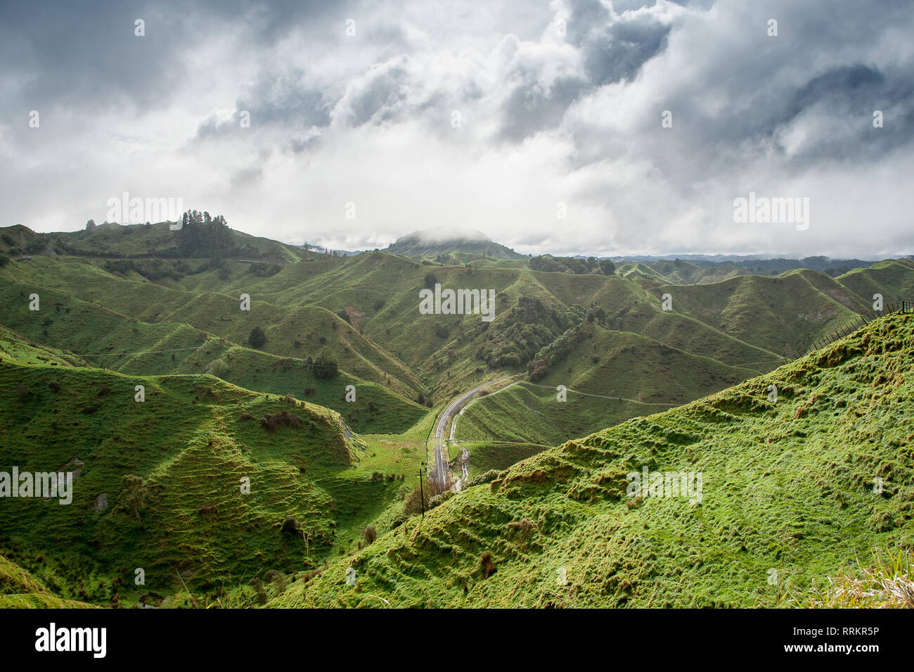 The Tahora Saddle, part of The Forgotten World Highway, North Island, New Zealand. Pastoral landscape, green steep sided hills and dark stormclouds - Stock Image
