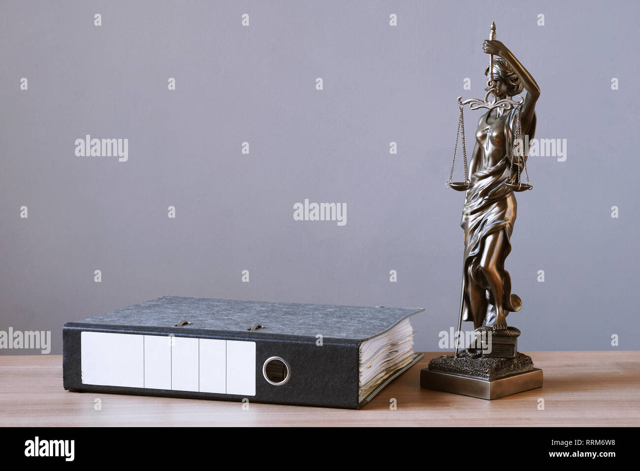 lady justice or justitia statue and file folder on desk - law and legal concept - background with copy space - Stock Image