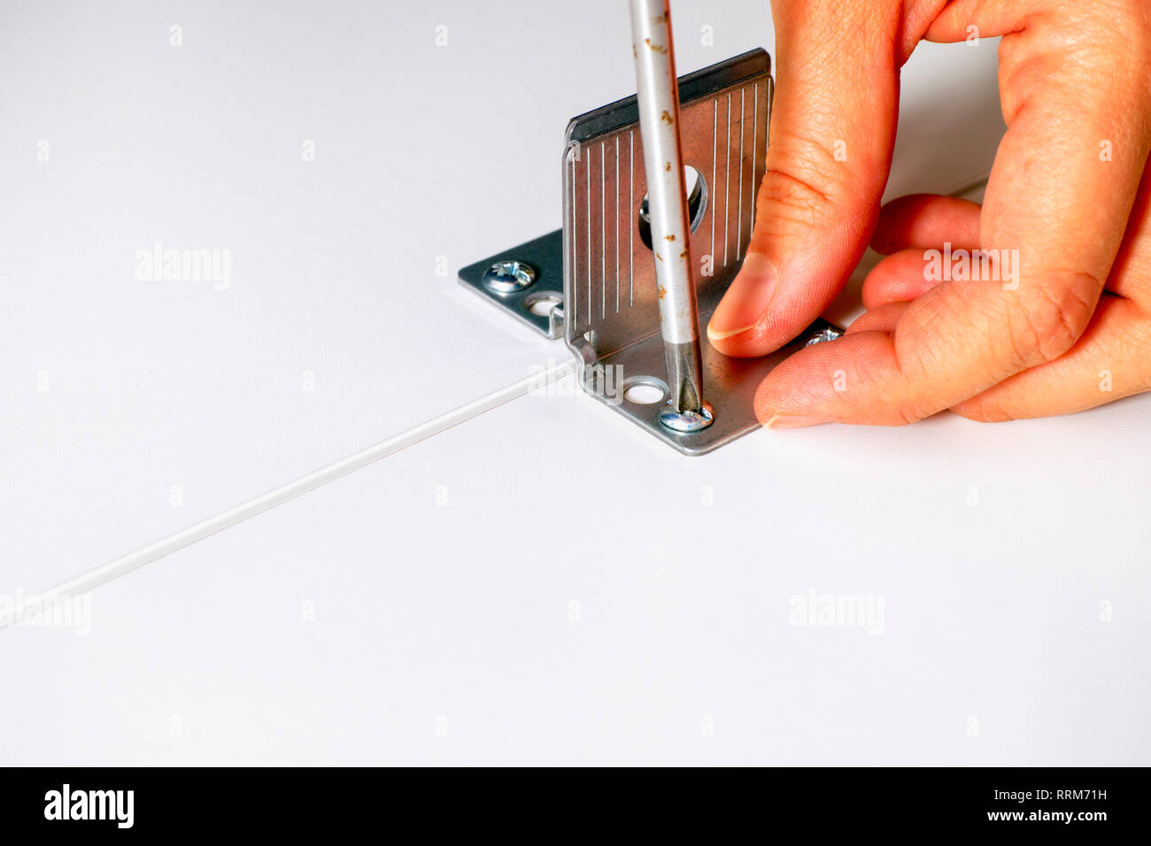Person hand with screwdriver twisting the screw into the furniture. Close-up. - Stock Image