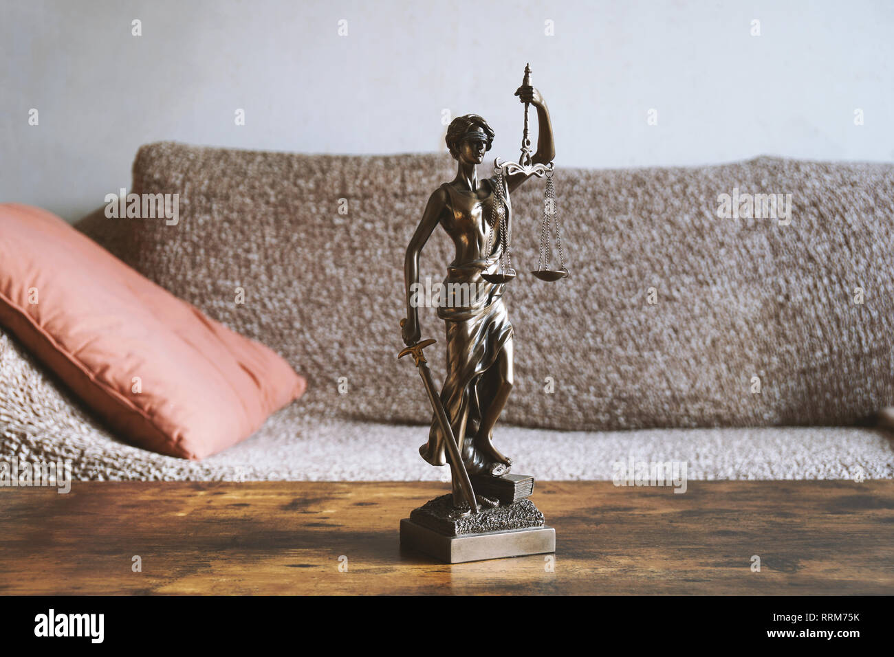 lady justice or justitia statue on table in living room - landlord and tenant law or right of residence concept - Stock Image
