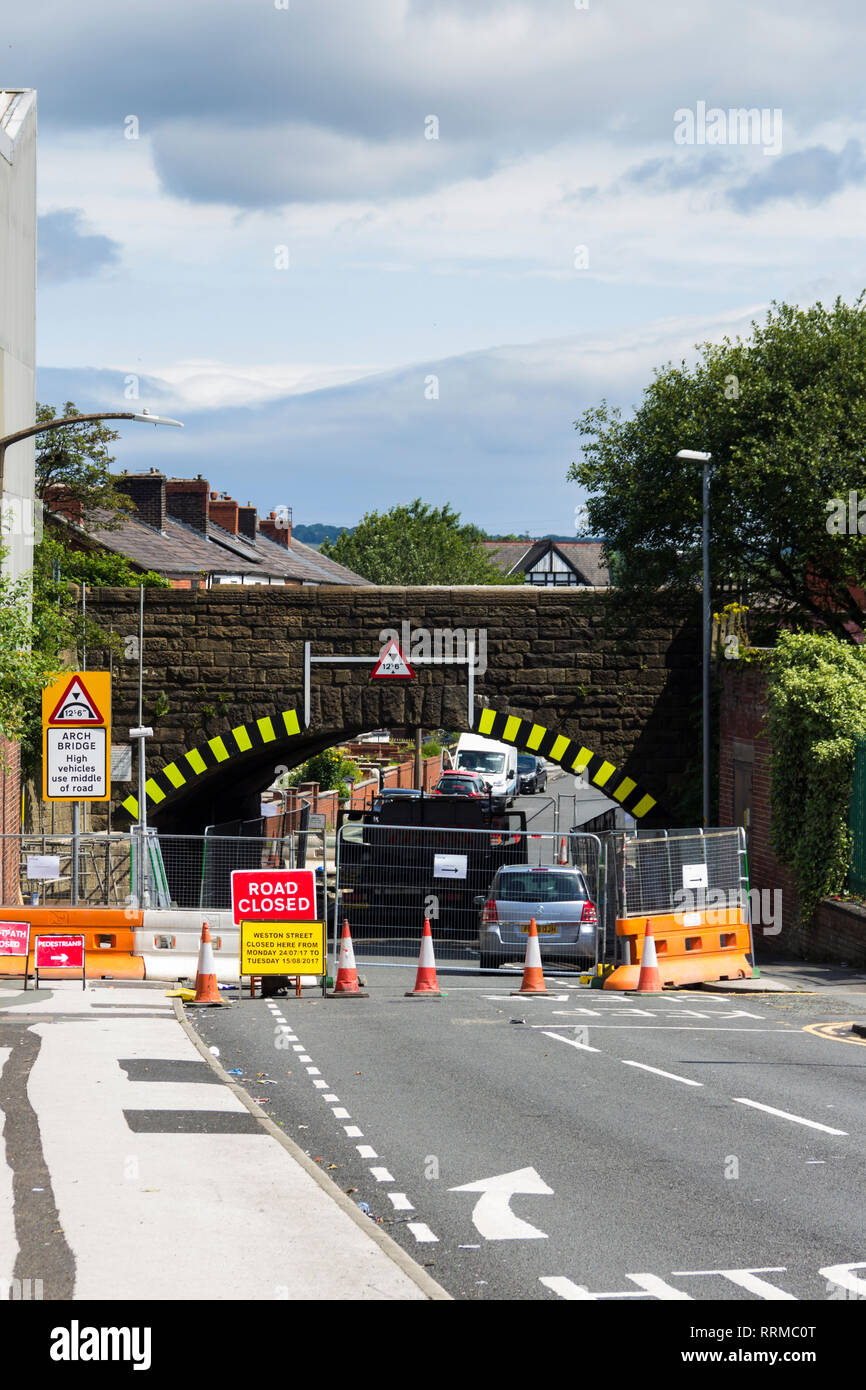 Low railway overbridge on Weston Street, Bolton, fully closed to road traffic for repair work lasting several weeks in the summer of 2017. Stock Photo