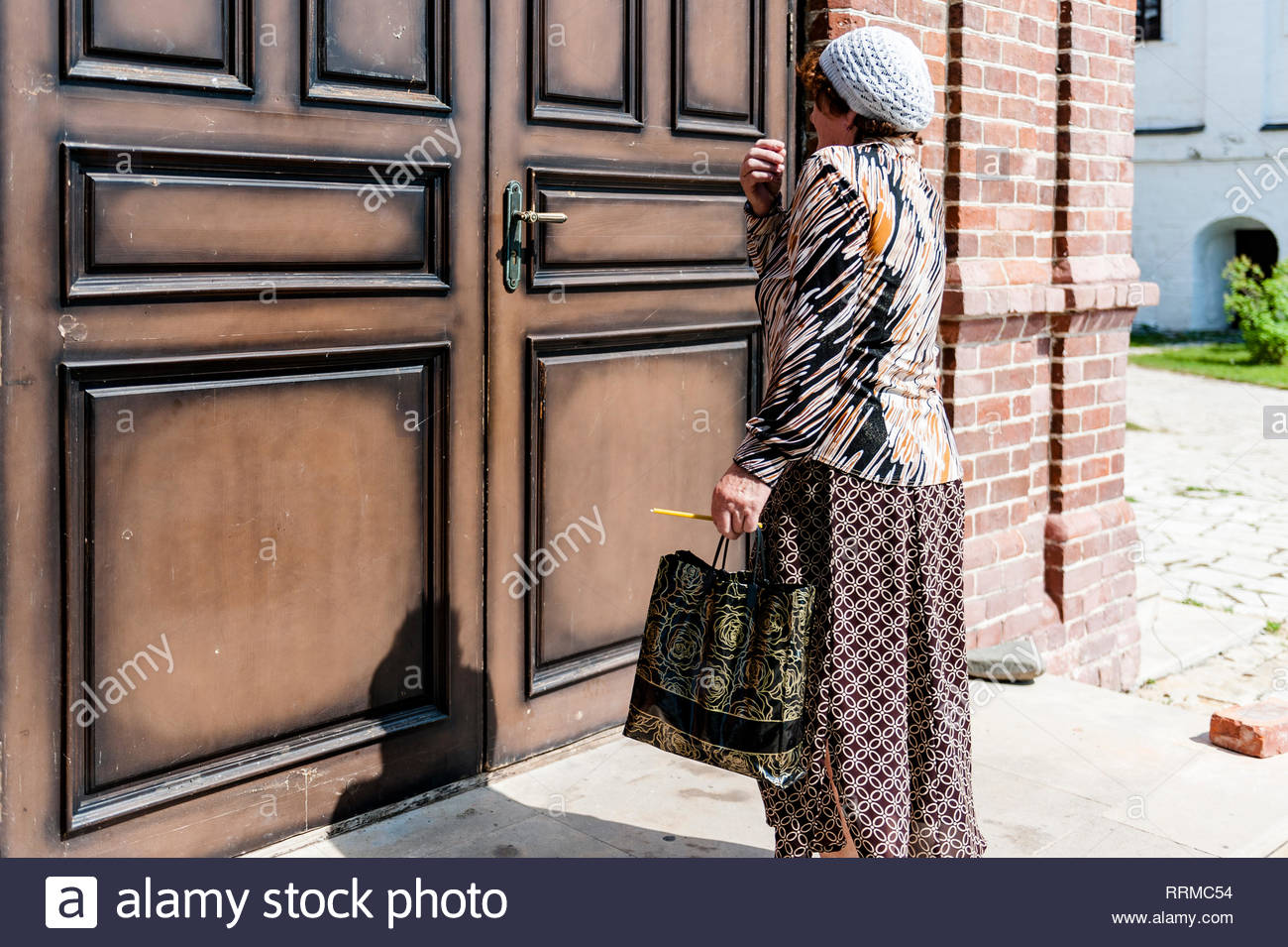 Russian woman with headscarf in front of church door - Stock Image