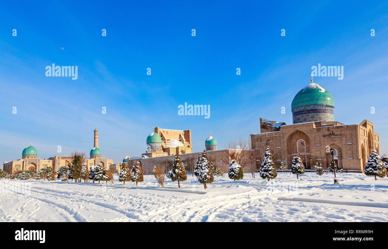 Snow and spruces with blue domes and minarets of muslim Hazrati Imam complex, religious center of Tashkent, Uzbekistan - Stock Image