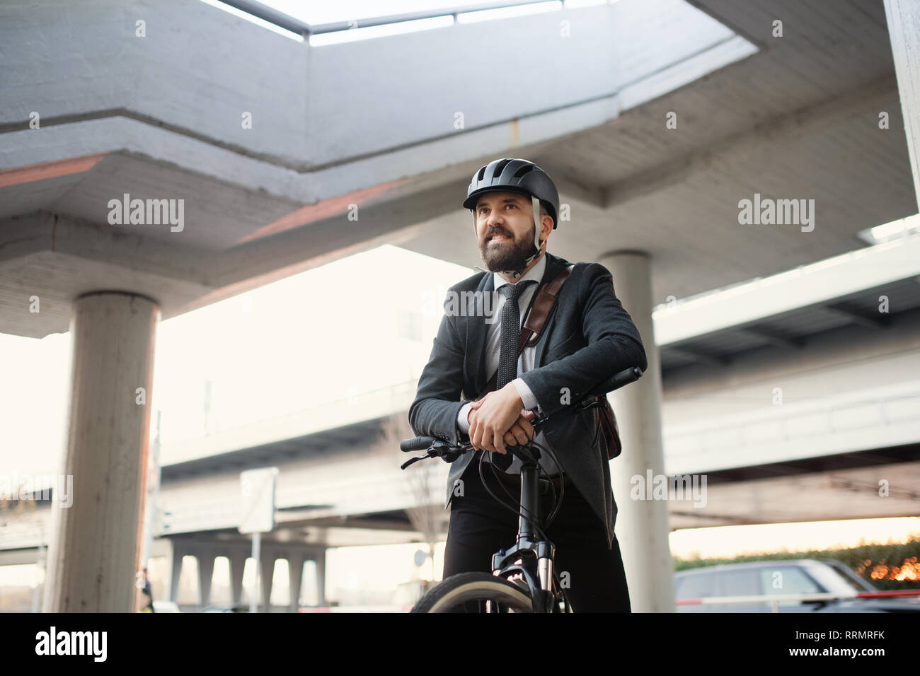 Hipster businessman commuter with electric bicycle traveling home from work in city. Copy space. Stock Photo