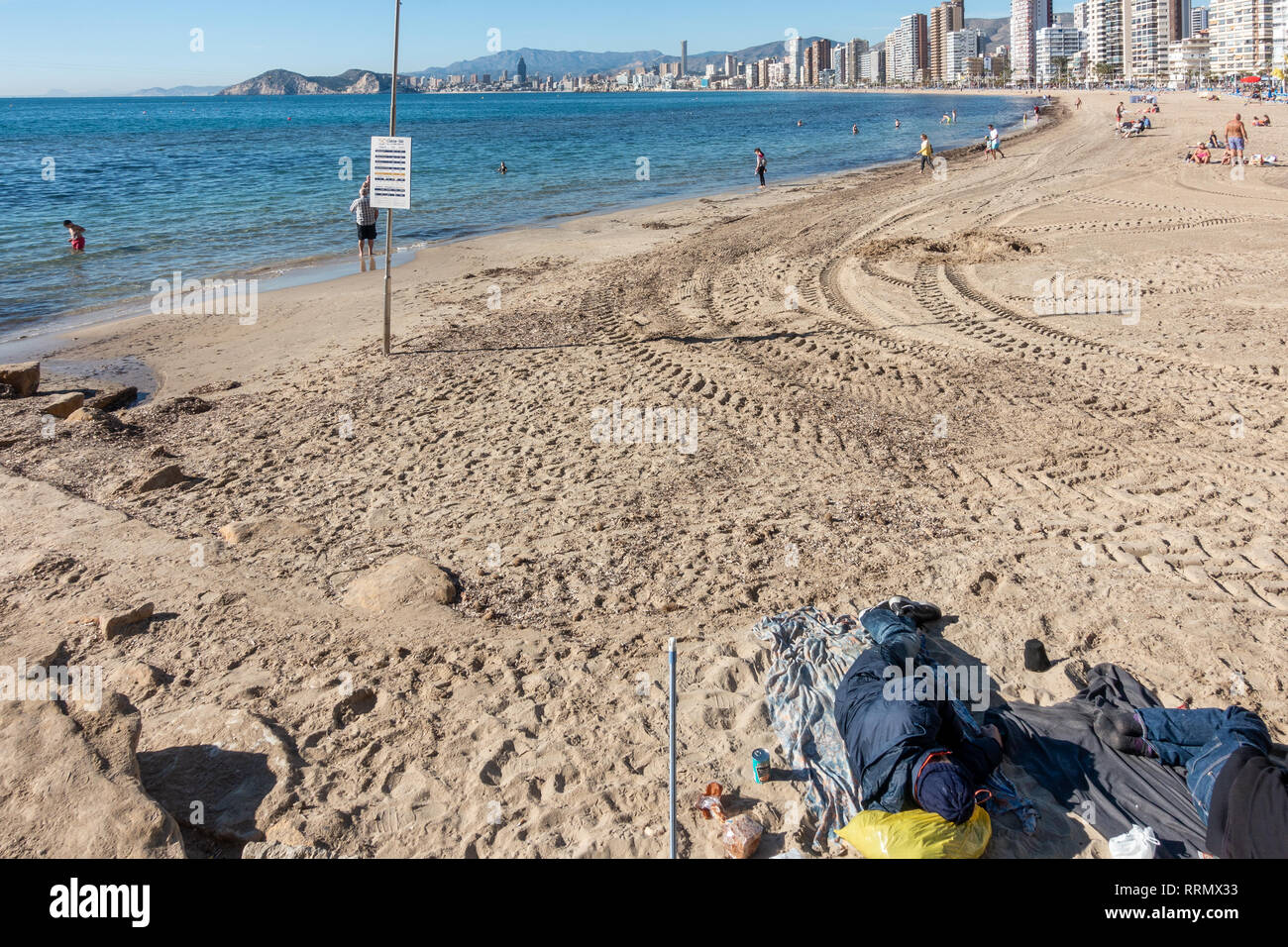 Rough sleepers on Levante beach in Benidorm amongst the holidaymakers just before Christmas Stock Photo