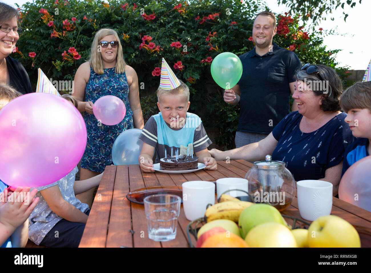 An excited boy ready for the cake tradition at family party. - Stock Image