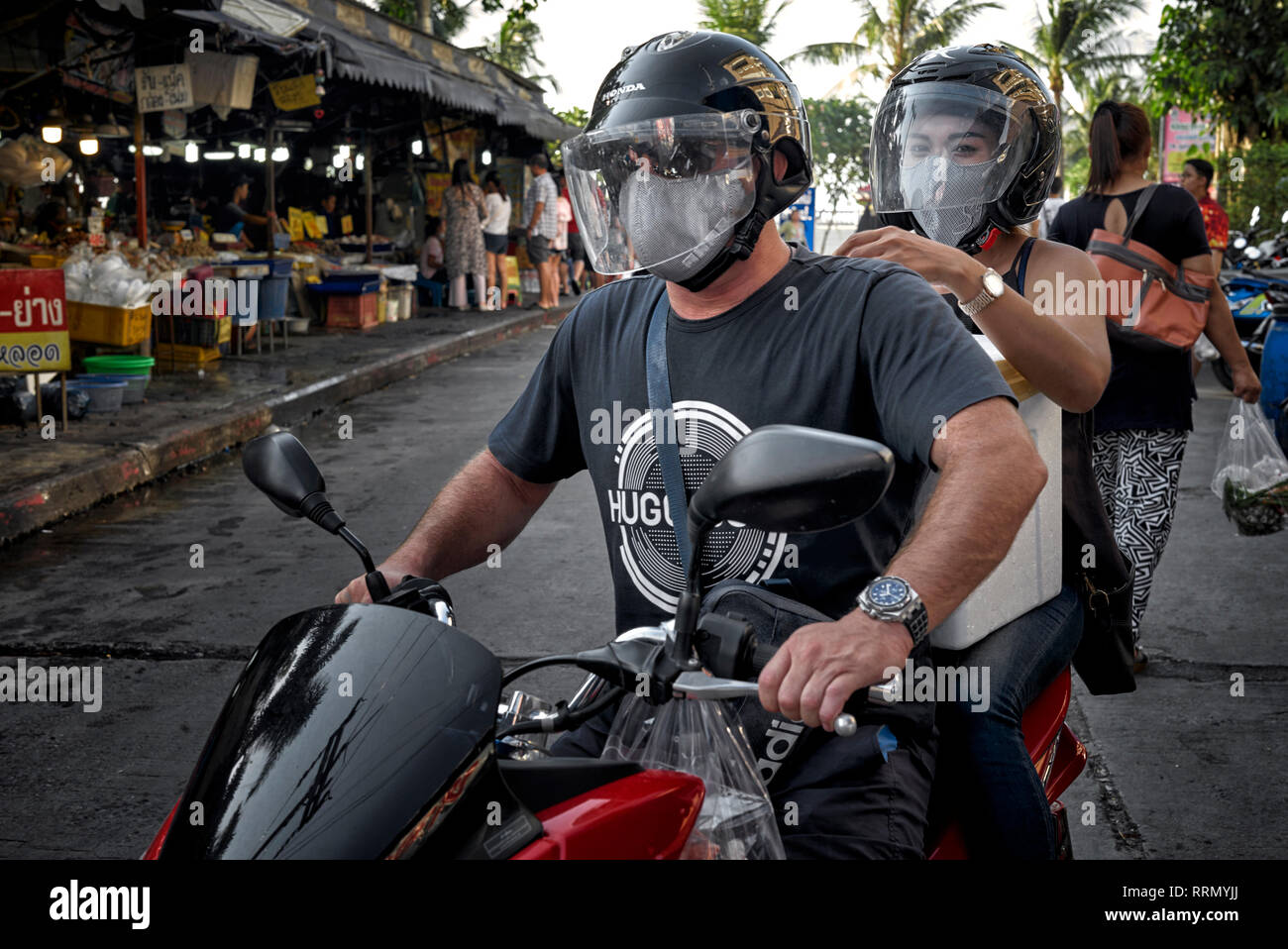 Couple motorbike. Man and woman riding a motorcycle and wearing safety helmet and face anti pollution mask - Stock Image
