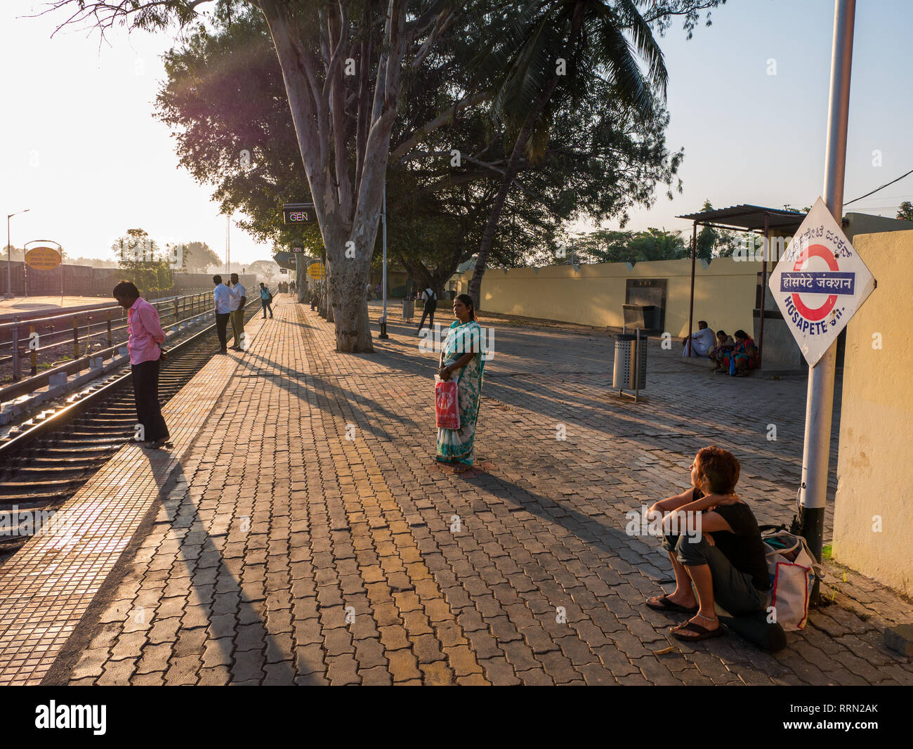 A female western tourist waiting for a train at Hosapete JN railway station near Hampi in India Stock Photo