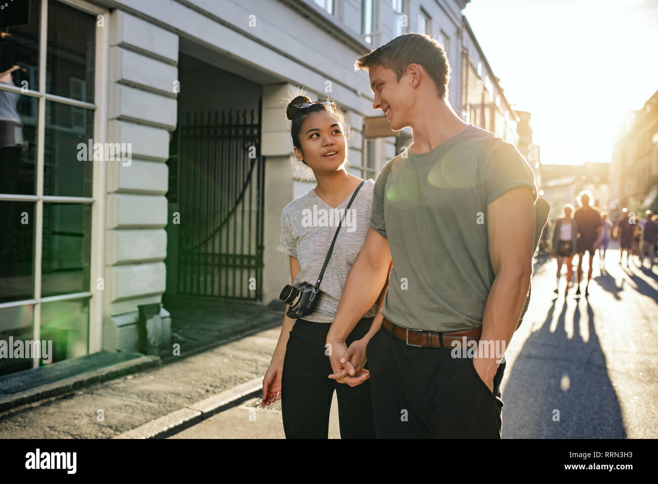 Smiling young couple exploring city streets together on foot - Stock Image