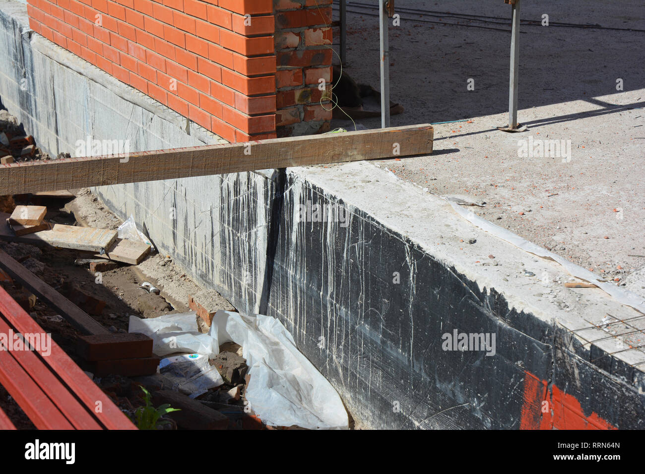 Foundation Waterproofing and Damp proofing Coatings.Waterproofing house foundation with spray on tar. Construction techniques for waterproofing baseme - Stock Image