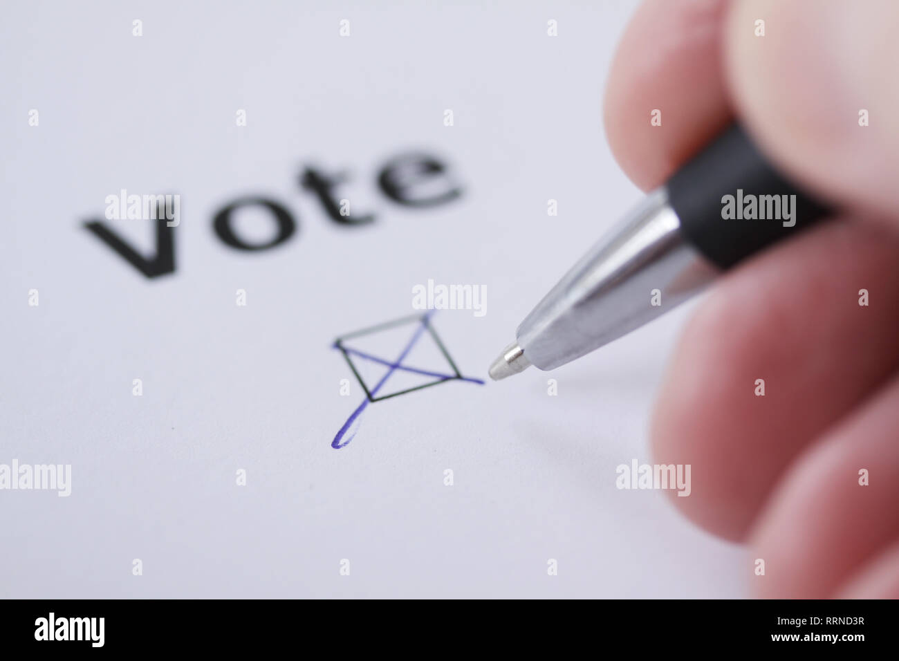 Hand of man voting - sets mark in check box with pen - hand, worrd and pen delibetrately blurred - Stock Image