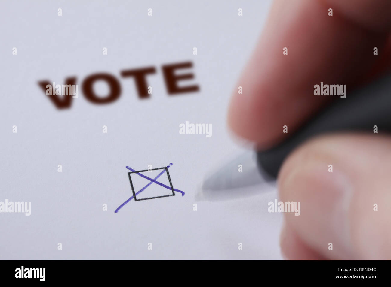 Hand of man voting - sets mark in check box with pen - hand and pen delibetrately blurred - Stock Image