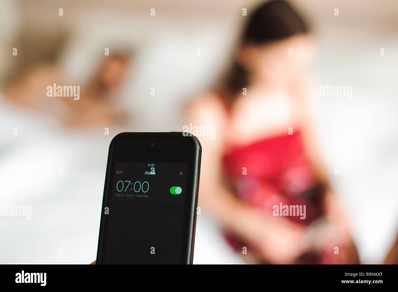 Beautiful young couple waking up with mobile alarm clock - Stock Image