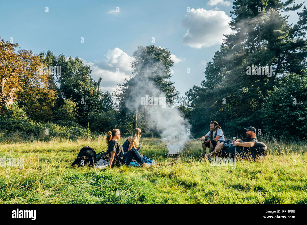Friends camping, relaxing around campfire in remote field Stock Photo