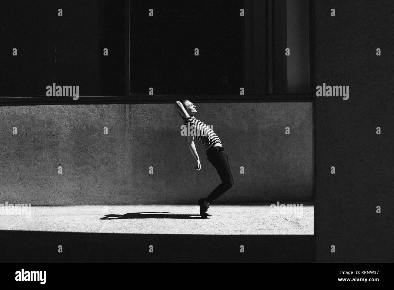 Young man dancing on urban sidewalk Stock Photo