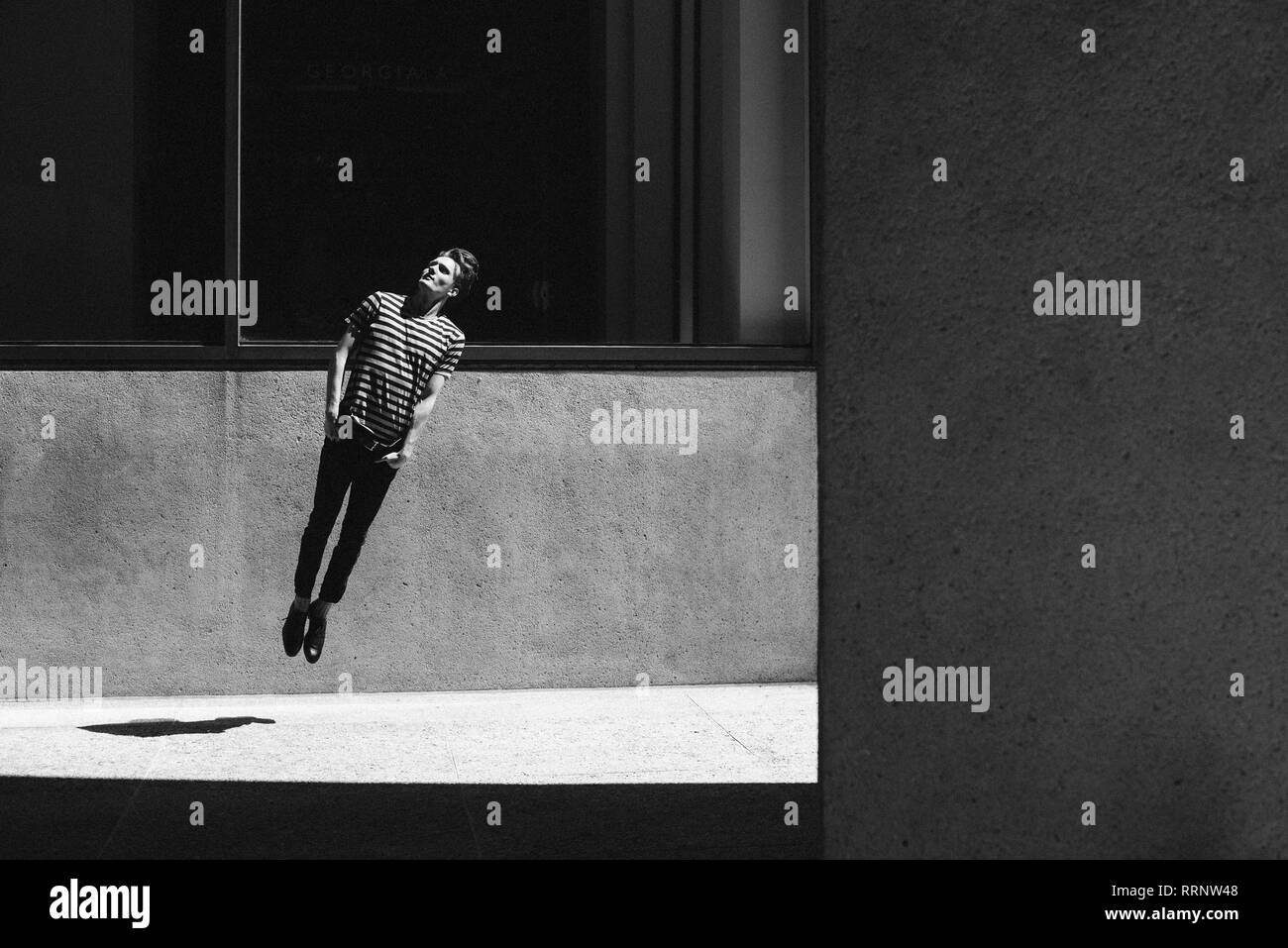 Young man jumping on urban sidewalk Stock Photo