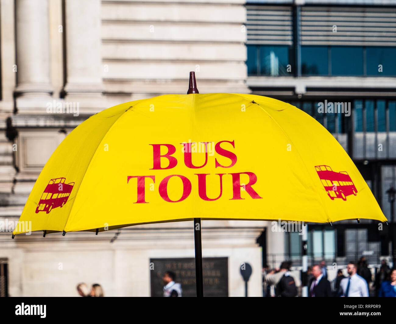 London Tourist Bus Tours - Yellow Umbrella marking a ticket stall for London Tour Bus tickets - Stock Image